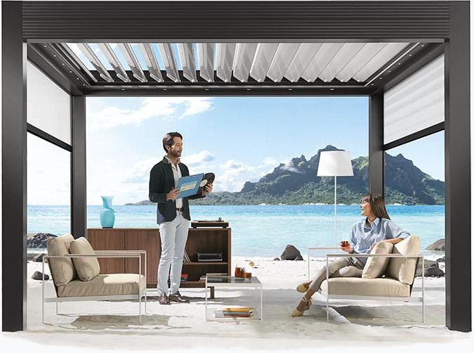 Paar in einer Lounge unter einem Lamellendach am Meer - mit geöffneten Dreh-Lamellen
