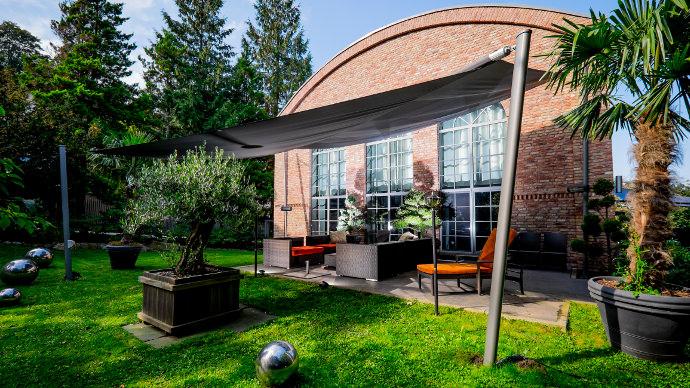 Marken Sonnensegel elektrisch aufrollbar über einer Terrasse im Garten