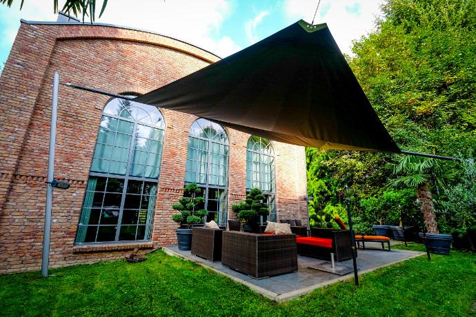 Sonnensegel elektrisch über einer Gartenterrasse