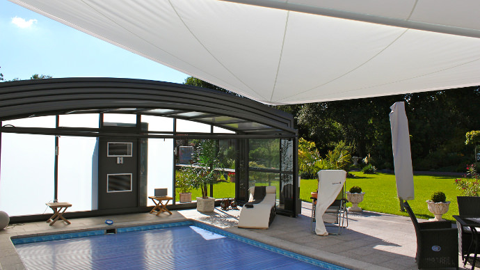 Elektrisches Sonnensegel in aufrollbar über einem Pool als Regen- und Sonnenschutz