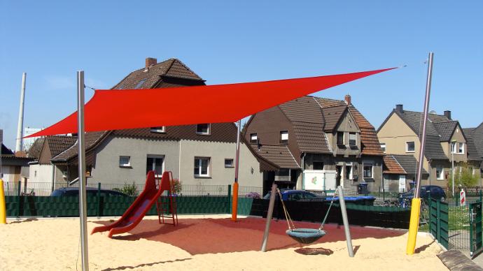 rotes Sonnensegel über Sandfläche im Kindergarten