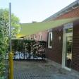Sonnensegel feststehend Lüdinghausen 2M / 2W gelbes Segel vor einem Haus